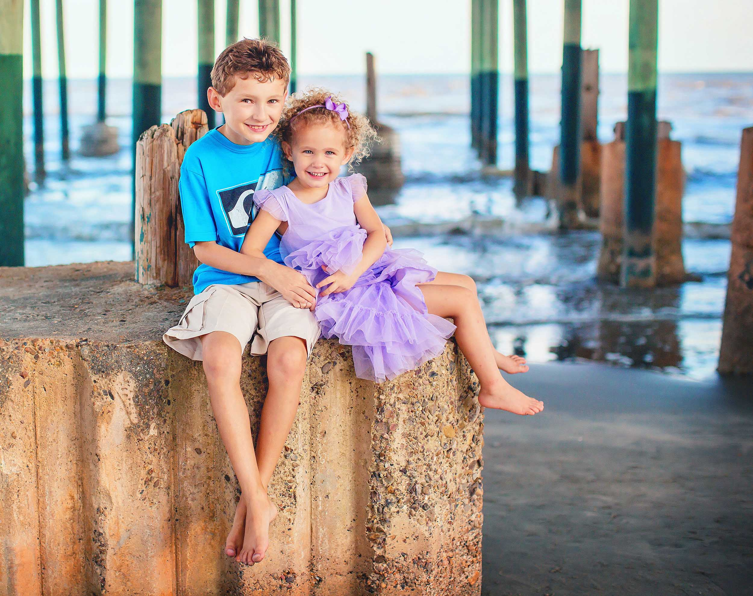 Siblings on pier in Galveston, Texas on the beach by spryART photography.