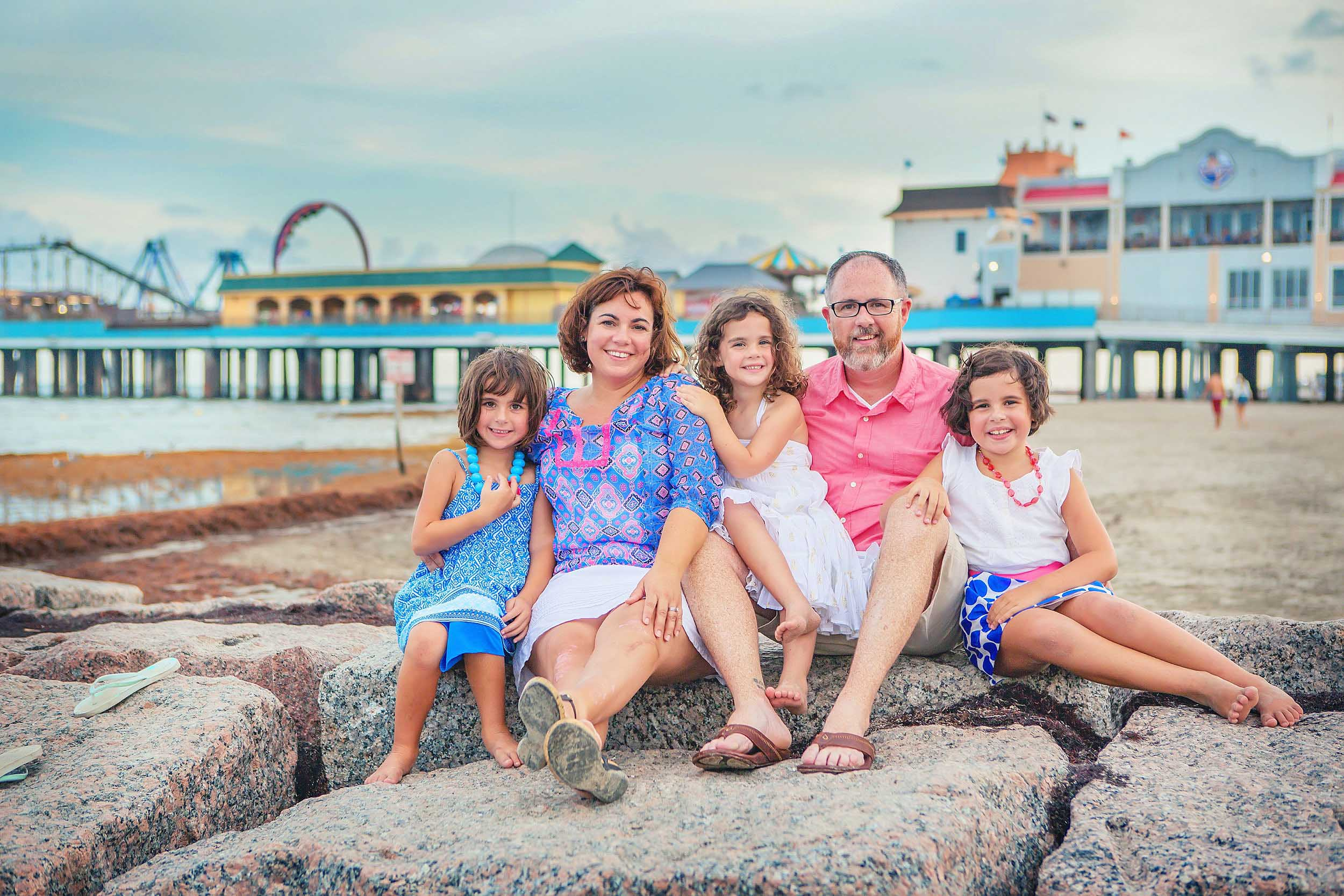 Beach portrait of family in Galveston with pleasure pier in the background.