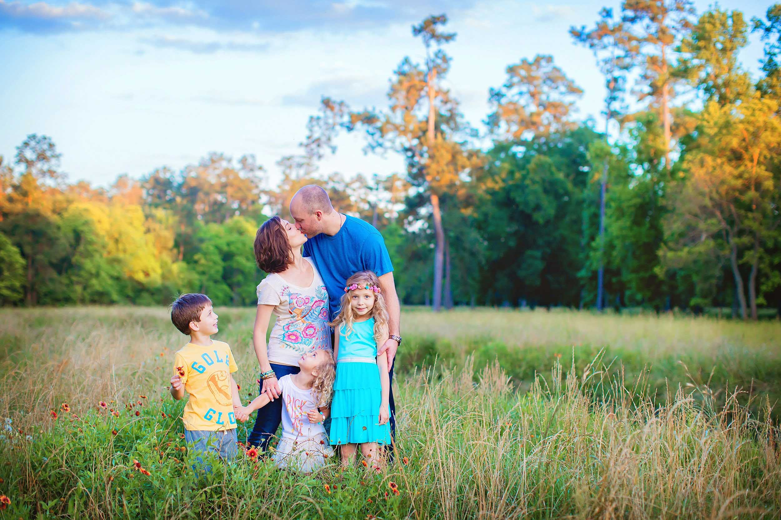 Family portrait with mom and dad kissing in wildflowers in The Woodlands, Texas.