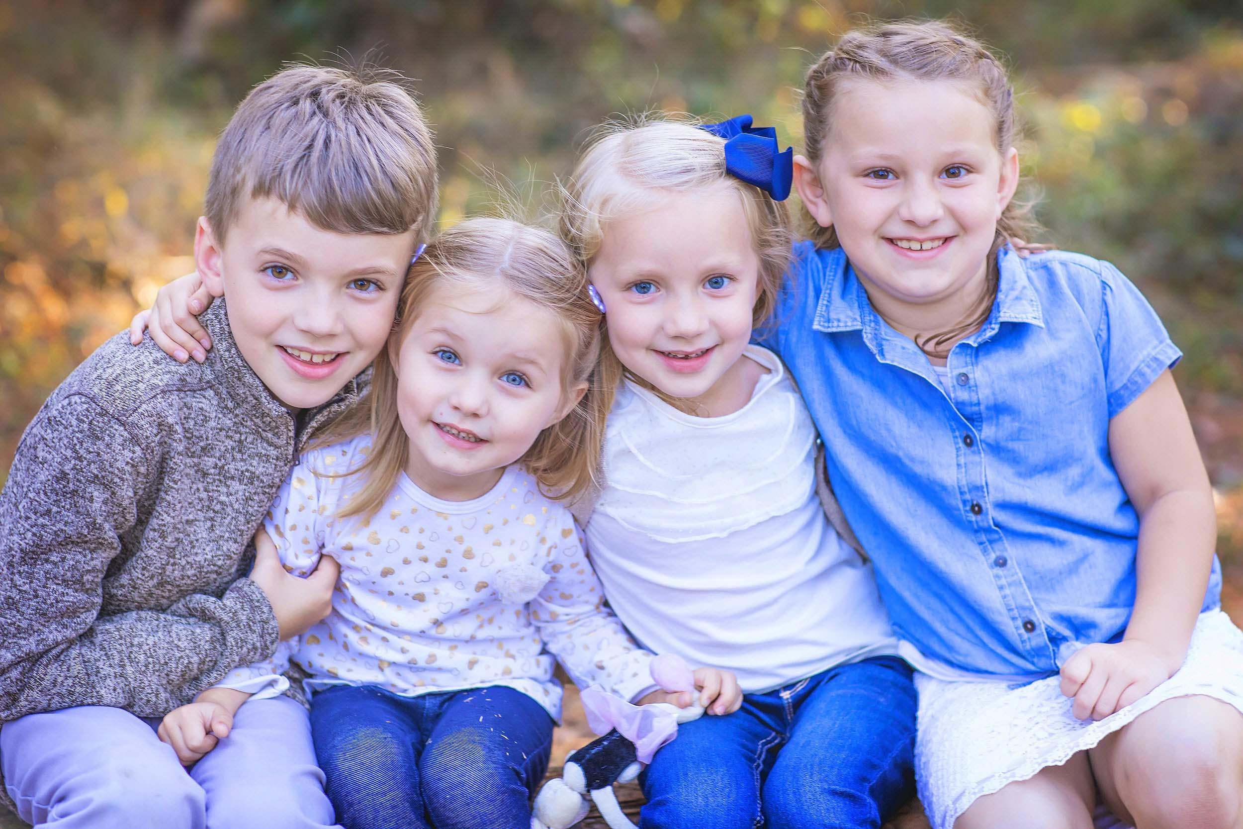 Outdoor portrait of four siblings hugging