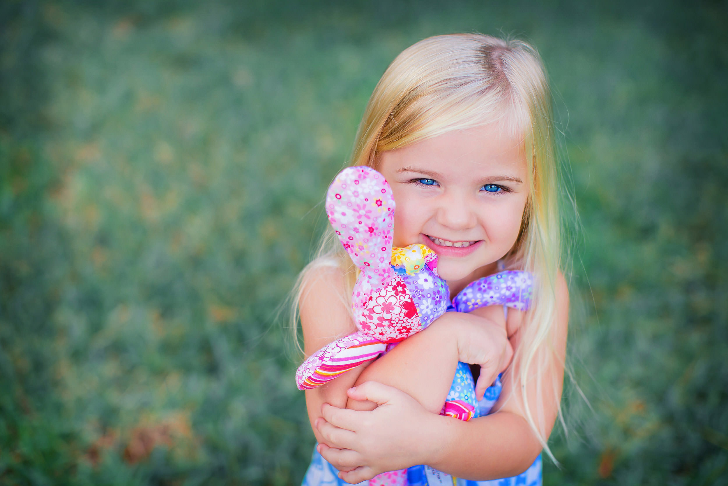 Young girl hugging favorite colorful stuffed bunny by family photographer spryART photography