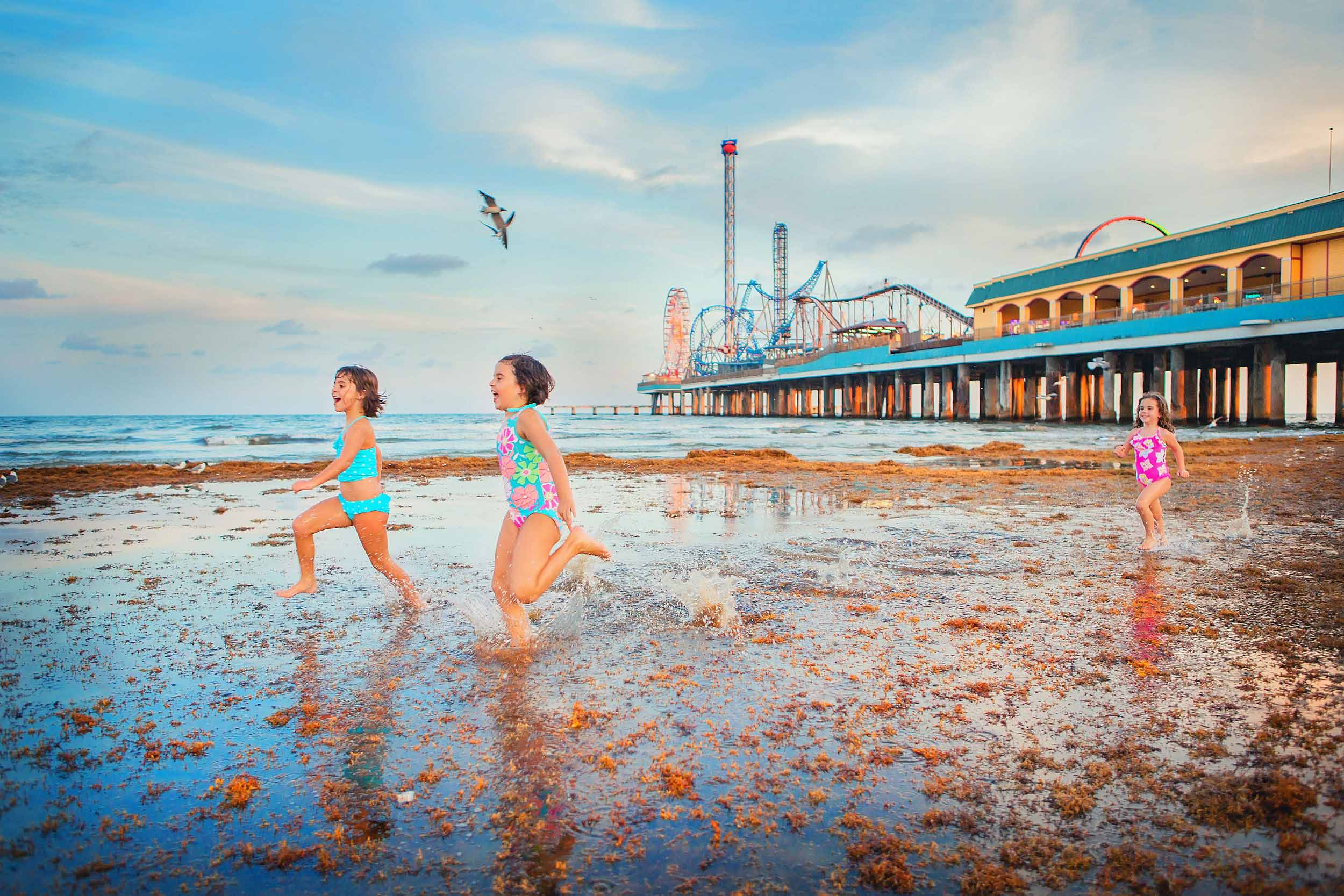 Young girls running on beach in Galveston Texas by Pleasure Pier by family photographer spryART photography