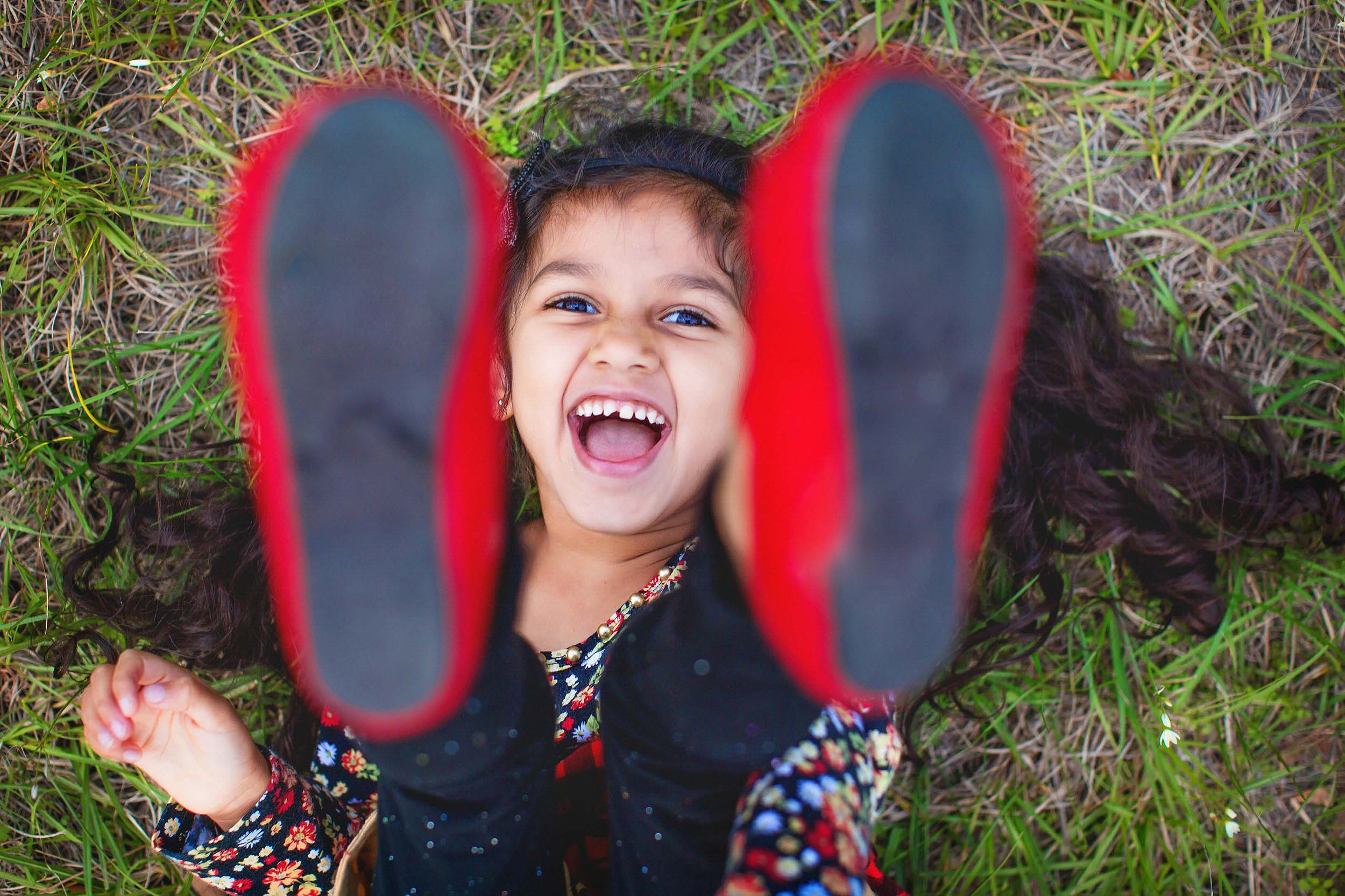 Lifestyle portrait of little girl in the grass laughing by spryART photography.