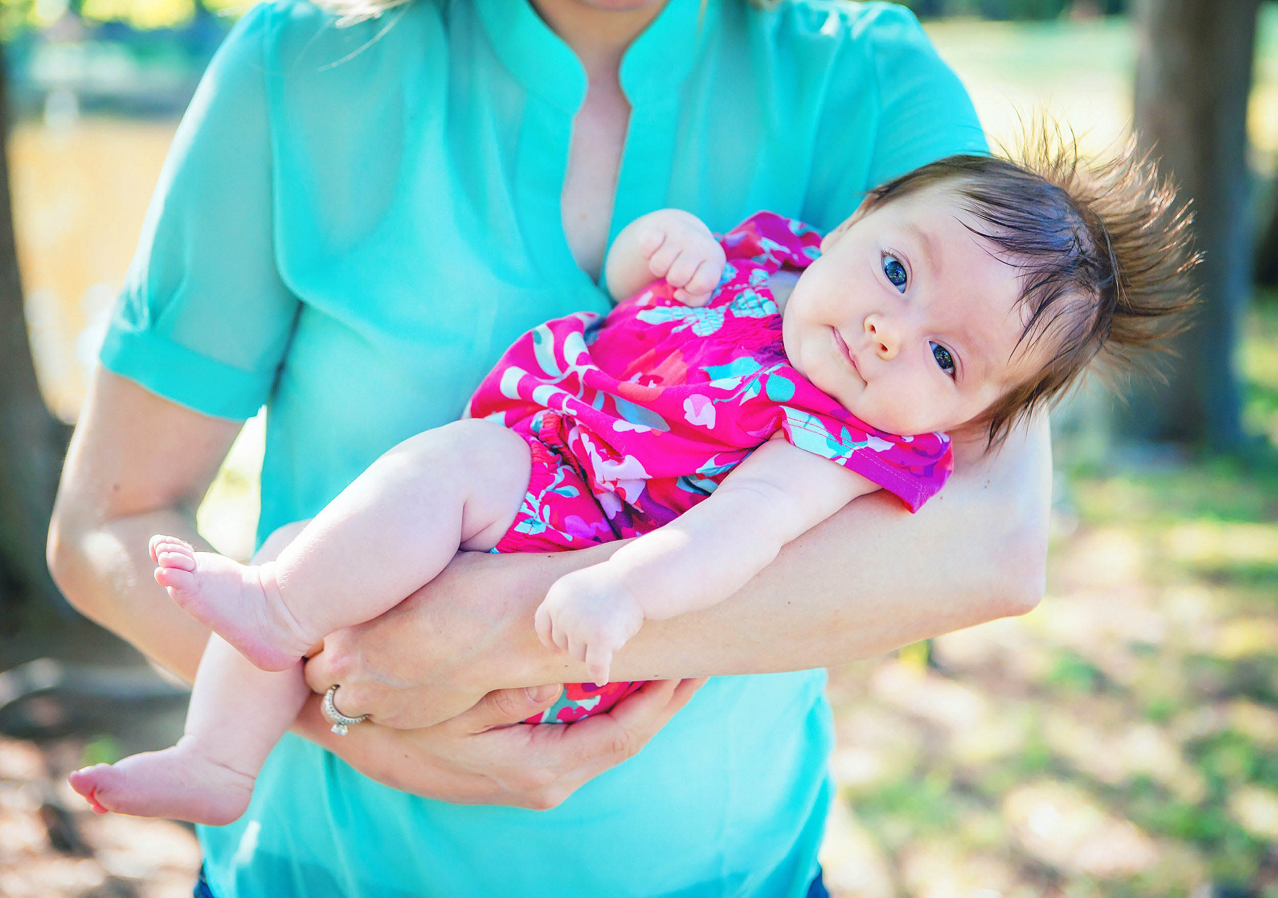 Funny portrait of infant with amazing hair in mom's arms in The Woodlands by spryART photography.