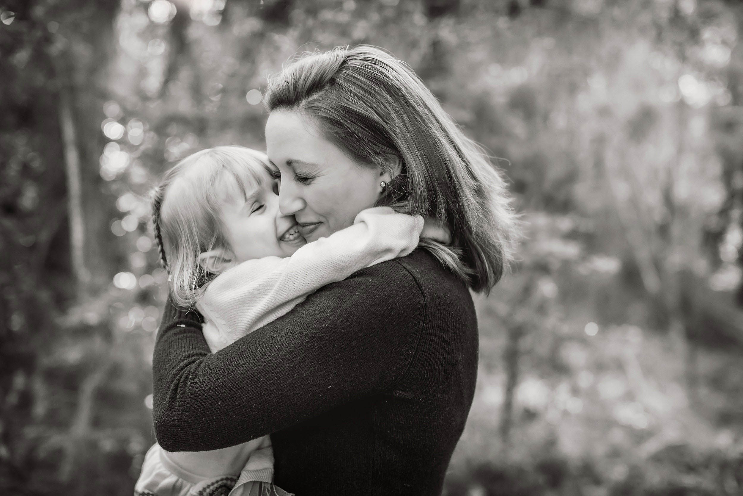 Black and white photograph of mom and daughter hugging.