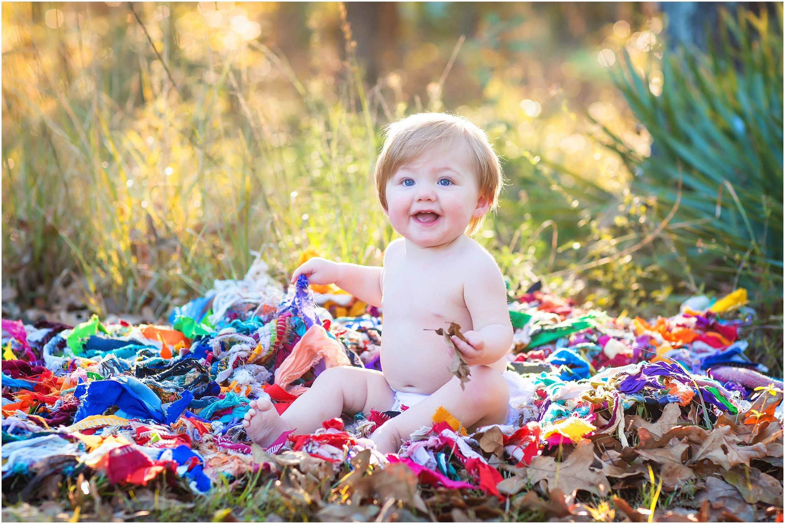 Photograph of a baby sitting in a field on a colorful blanket in The Woodlands, Texas taken by Houston Family Photographer spryART photography.
