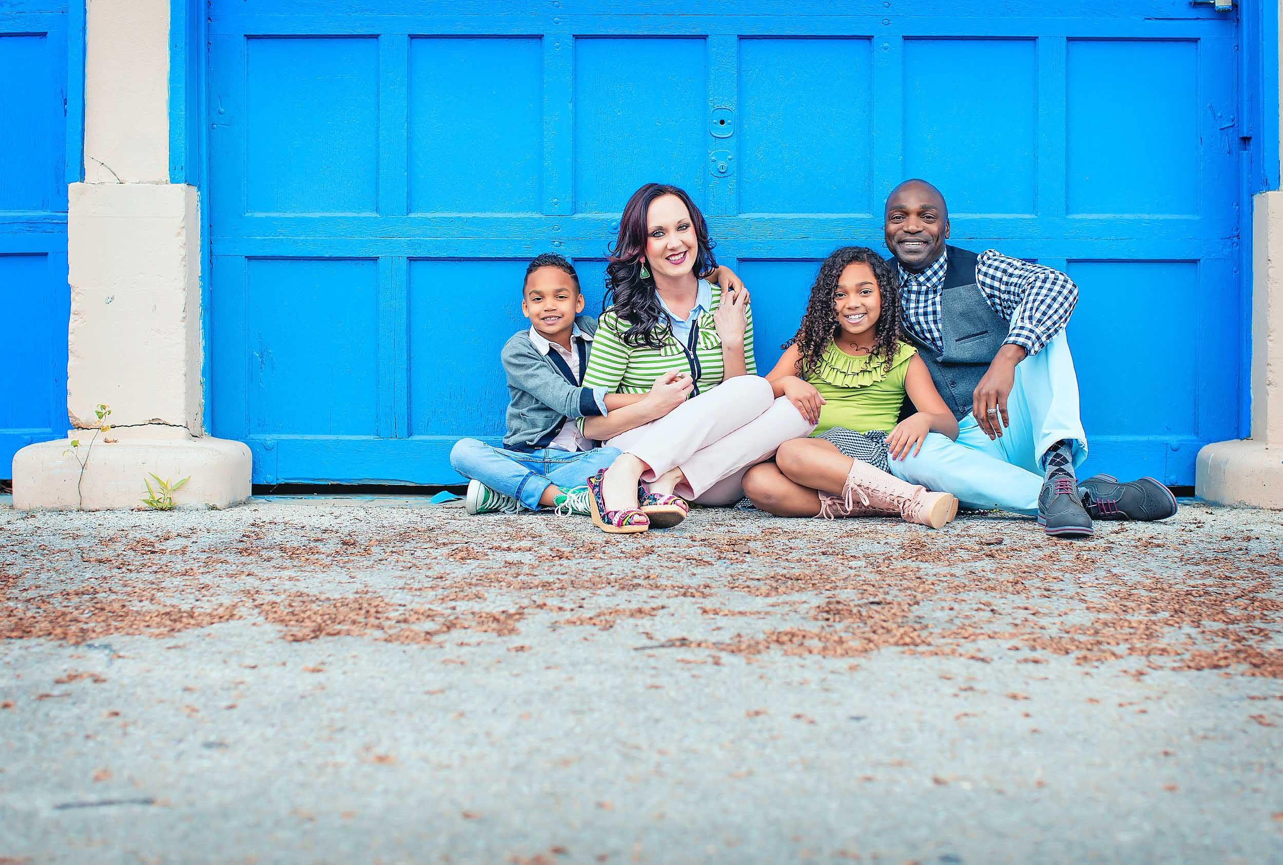 Coloful family portrait against blue garage door by Houston Family photographer spryART photography