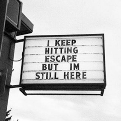 "A photo of a sign attached to the side of a building that reads, ""I keep hitting escape but I'm still here.�"