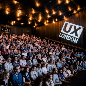 """A photo of a many people sitting in a large auditorium with a sign behind them that reads, """"UX London.�"""