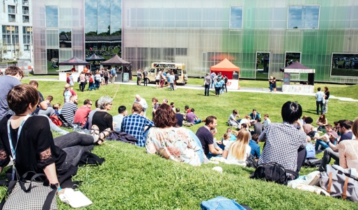 A photo of groups of people sitting outside on a grassy area right next to a large building.
