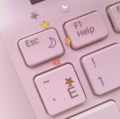 An up close photo of a keyboard with the escape and help keys visible. Some star confetti in on the keyboard.