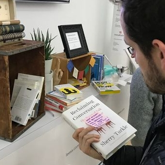 A photo of a man looking at a book near a small bookshelf.