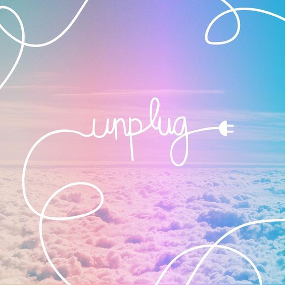 """A bird's eye view of the clouds with the word """"unplug"""" written with an unplugged cord."""