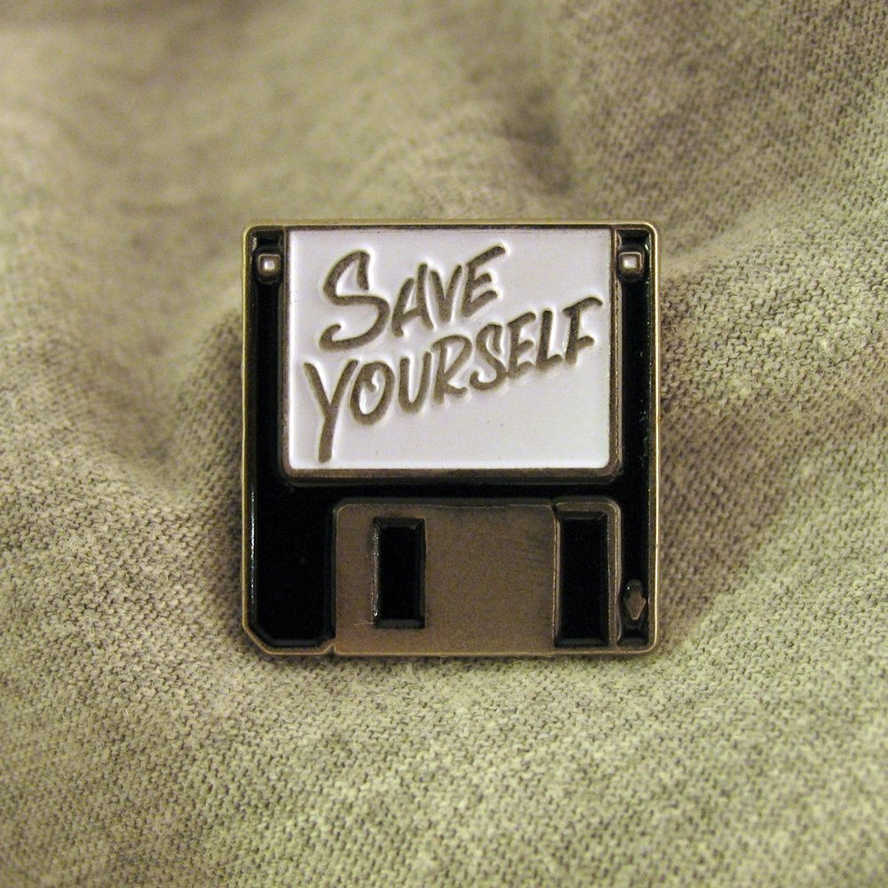 "A small metal pin shaped like a floppy computer disc that says, ""Save Yourself."""