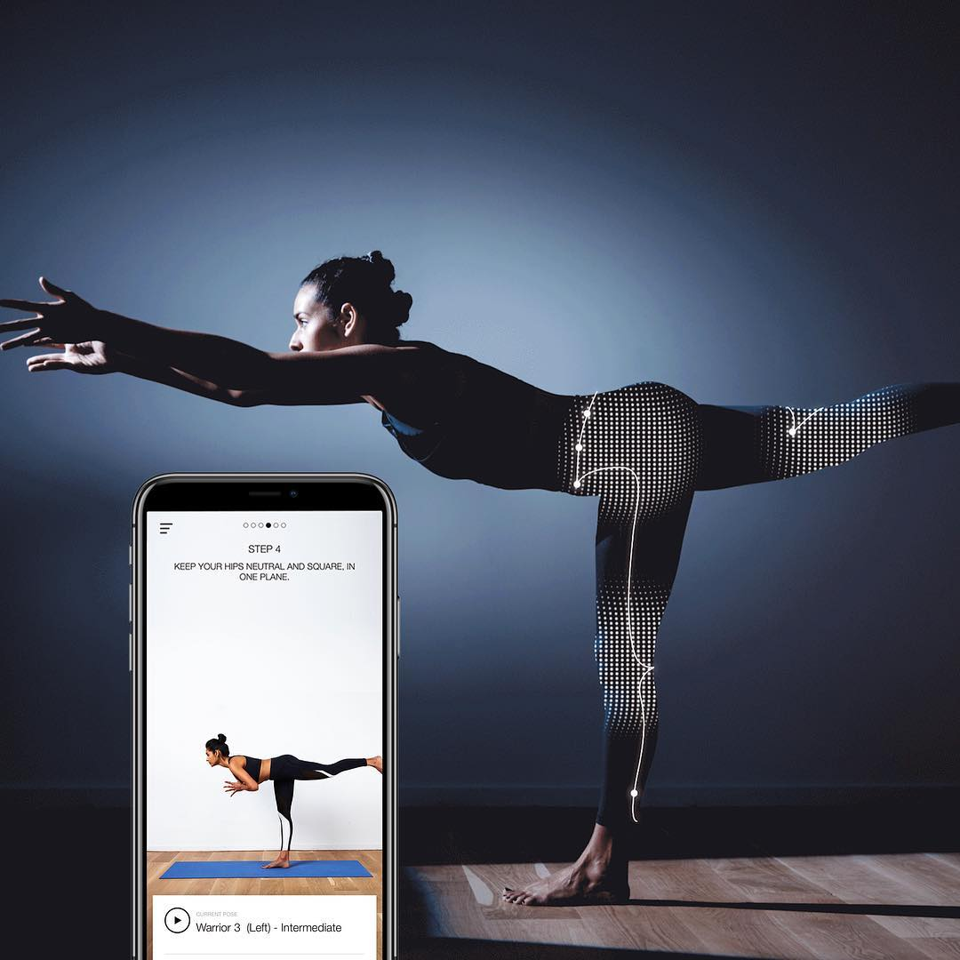 A woman doing yoga while wearing tech-enabled yoga pants. A smartphone is below her with the NADI X app.