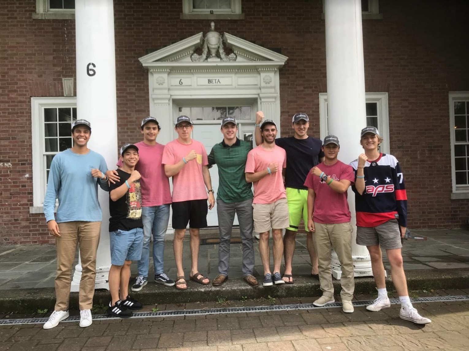 """A group of college students standing in front of a fraternity house wearing hats that say """"Mindhood"""" on them."""
