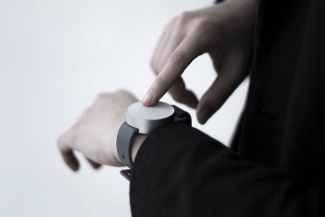 Photo of a man wearing a Dot Braille smartwatch and using his finger to read the Braille.