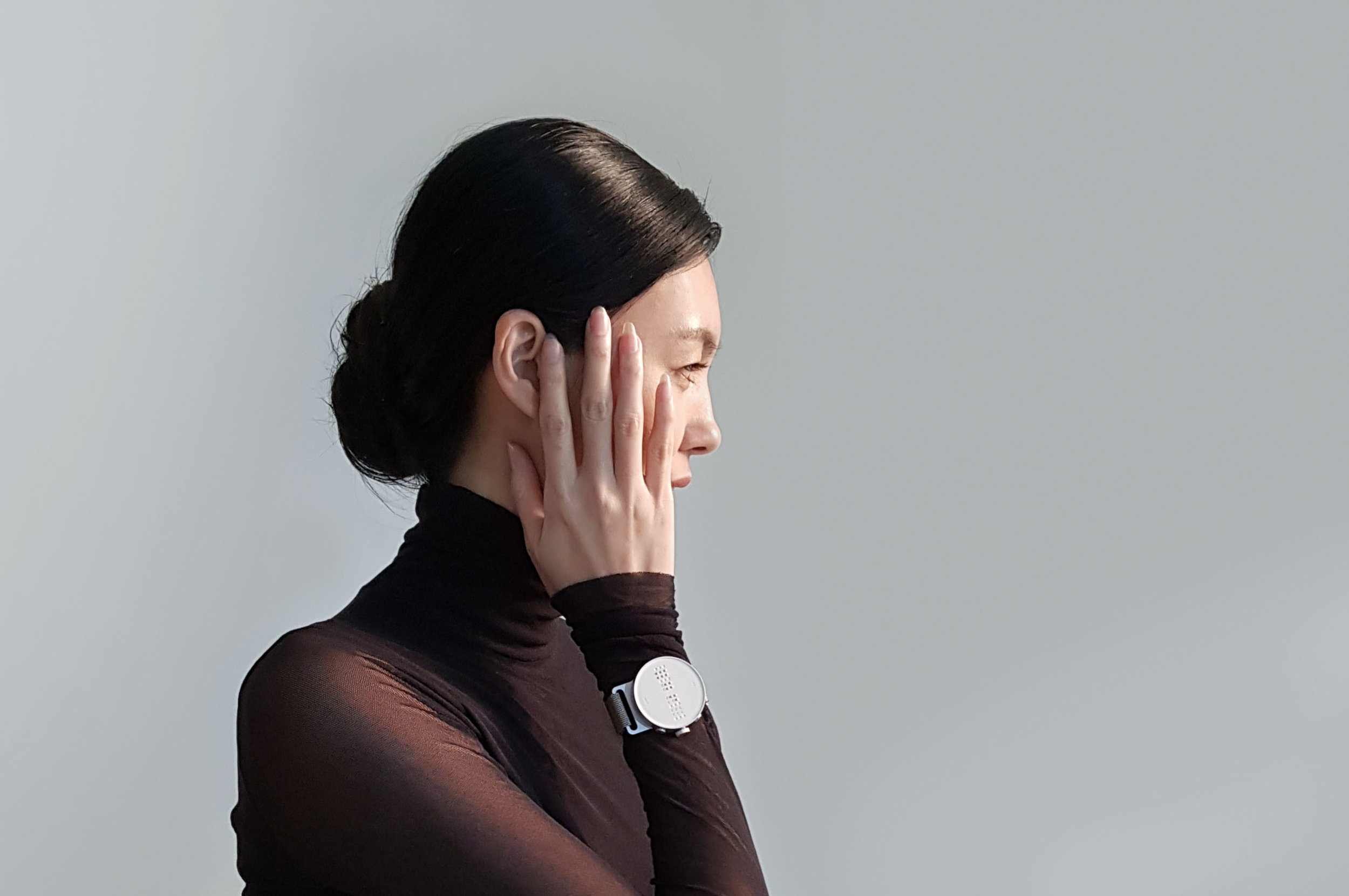 Photo of a woman wearing a Braille smartwatch.