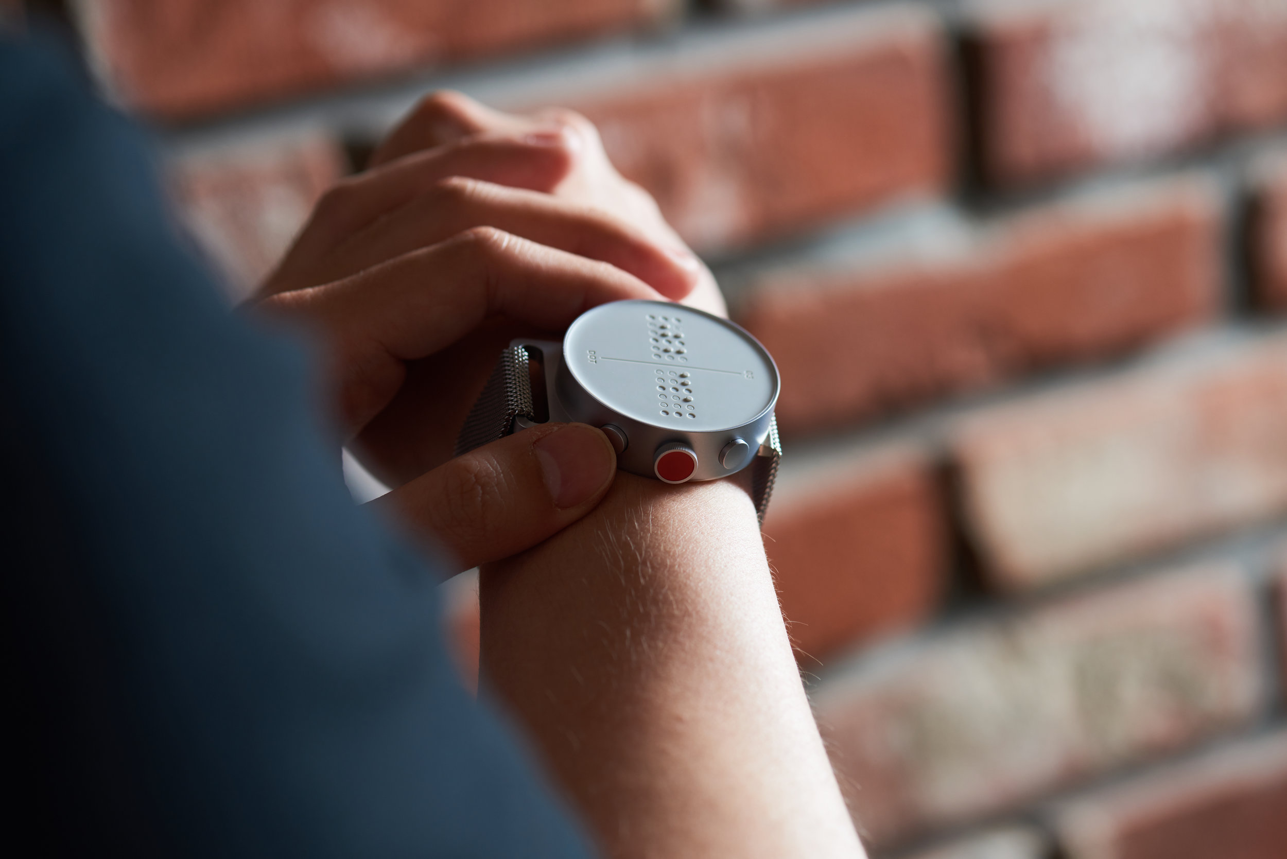 A photo of a person wearing a Braille smartwatch while holding the sides of the watch lightly.