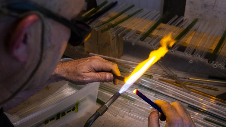 A propane torch is used to polish the straws