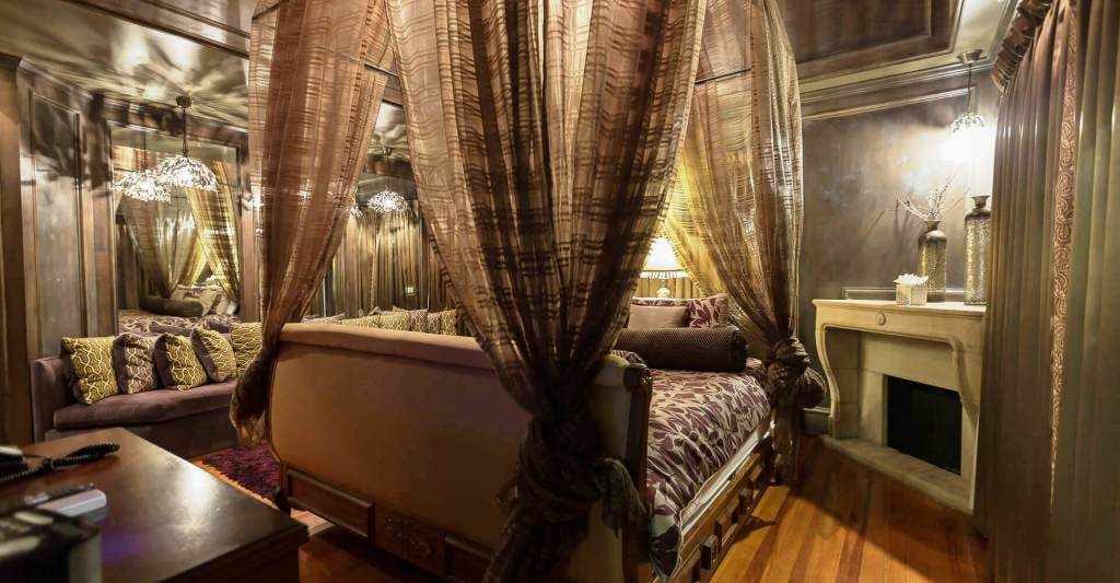 RENAISSANCE & BRIDAL SUITE - Featuring a king floating sleigh bed, this king cupola suite features a custom purple velvet sofa, mirrored walls, and more.