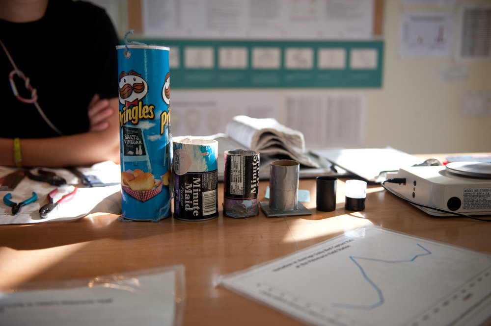 A Pringles can,frozen juice boxes, and empty film canisters are used to hold birds of various sizes during the weighing process. Biologists discovered that when birds are placed head-first into the containers they instinctively hold still