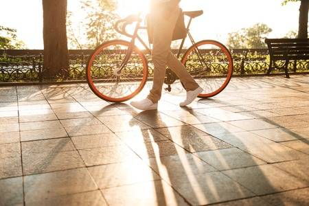 85242974-cropped-picture-of-handsome-young-african-man-early-morning-with-bicycle-walking-outdoors-.jpg