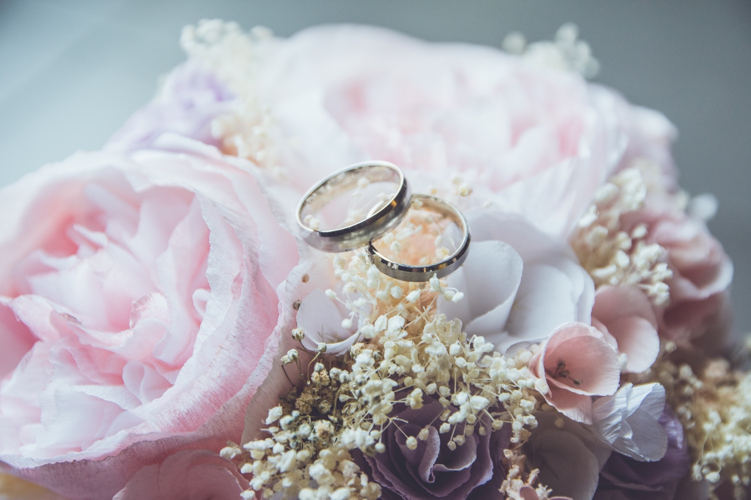 Wedding bouquet with wedding bands on top - wedding planning Absolutely Chic Events