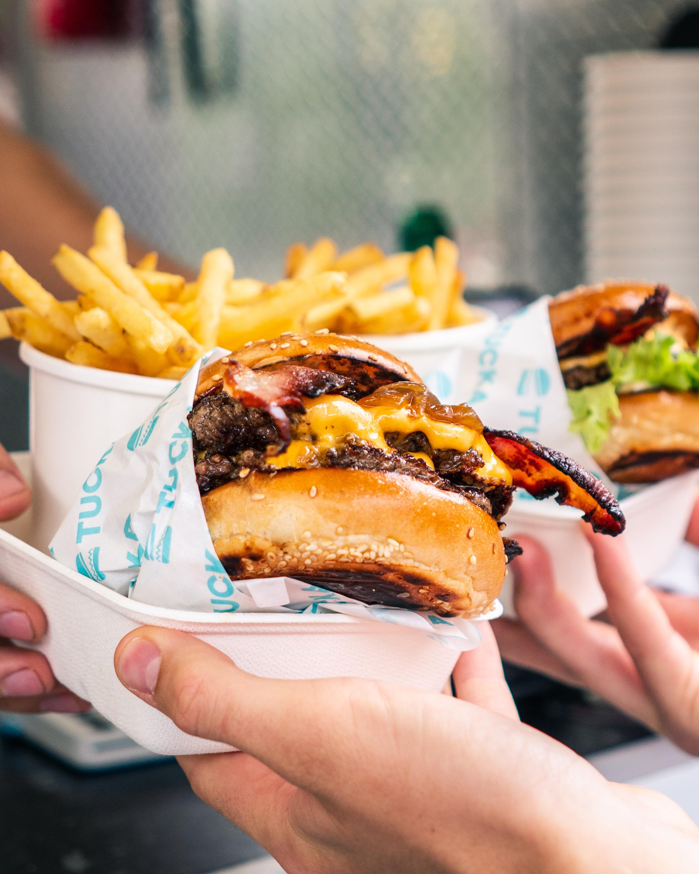 threeshades burger being passed.JPG