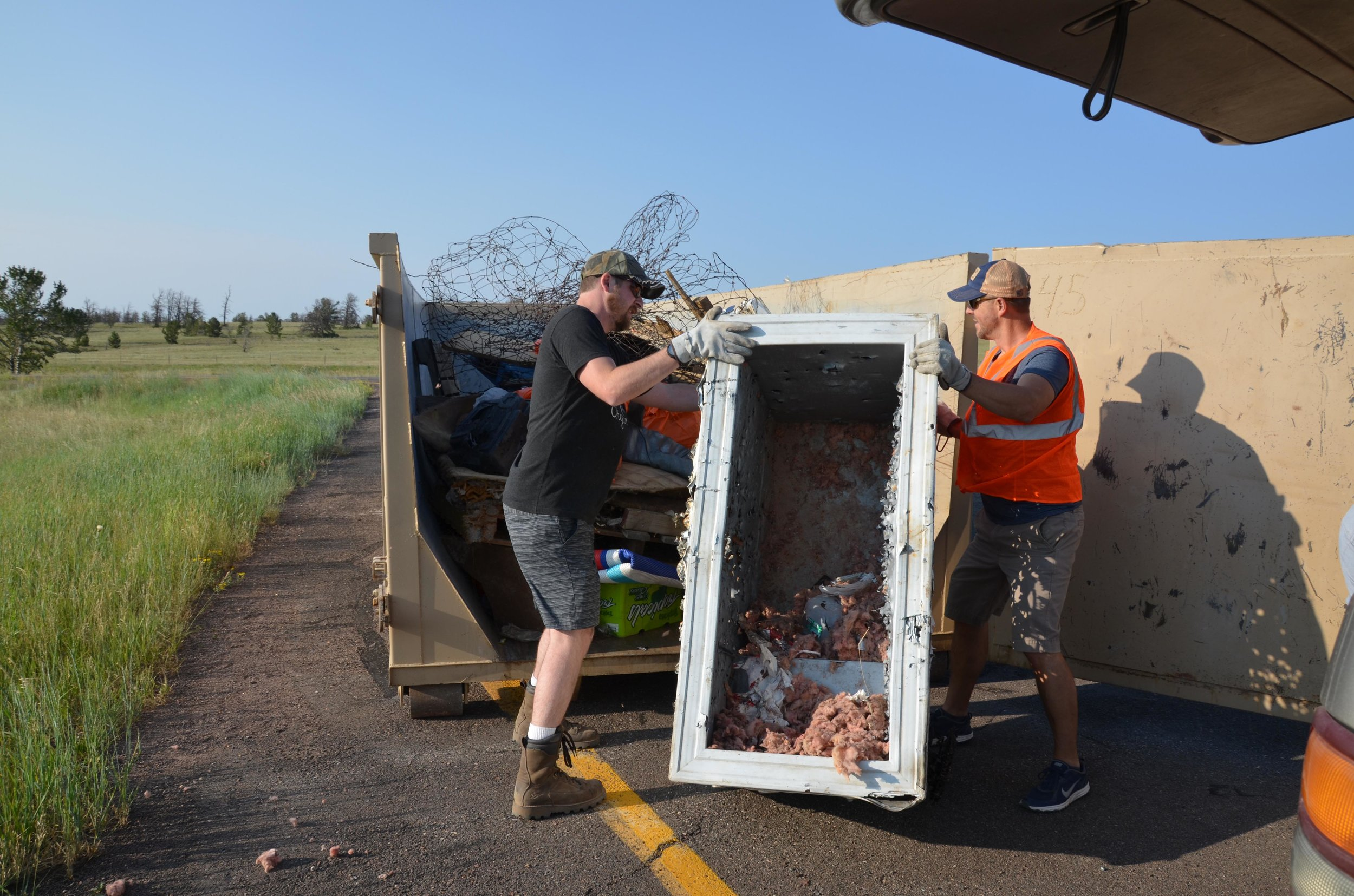 Volunteers move a discarded refrigerator into a dumpster during the 2018 Pole Mountain Cleanup. (Photo by Willow Belden)