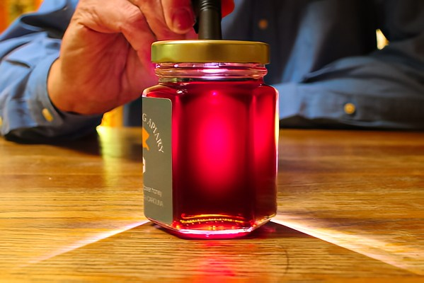 """NC Flying Pig Apiary """"Purple Honey"""" lit by a high-intensity LED flashlight, the honey glows in various shades of red, purple, and pink. © Rusty Burlew."""