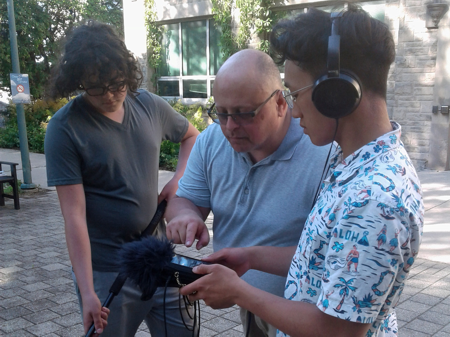 Film Director (c) instructs two youth actors/crew members at UWO location.
