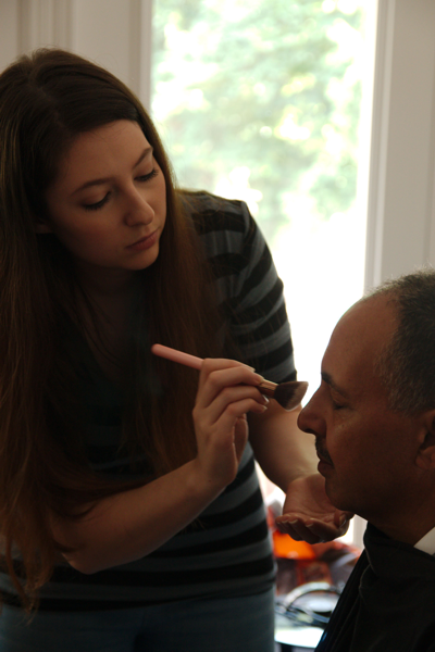 Helena Rose applying make-up on actor Lee Highgate.