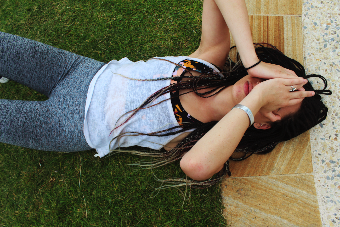 [image description: Ria in activewear lying on grass and her head is on a sandstone pavement. She is covering her face with her hands.]