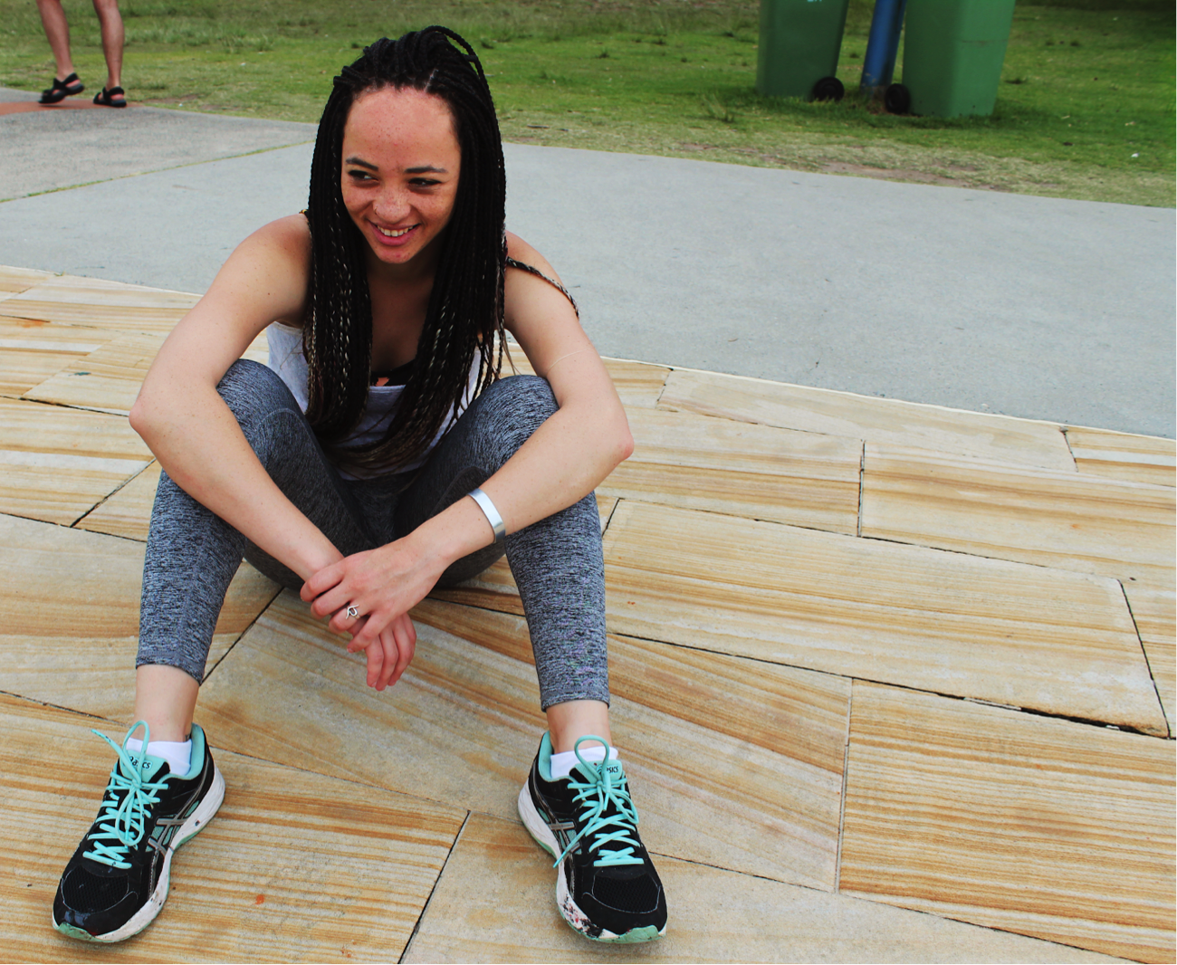 [image description: Ria is sitting on a sandstone pavement with her knees bent. Her arms are placed casually over her knees and she is smiling and looking away from the camera].