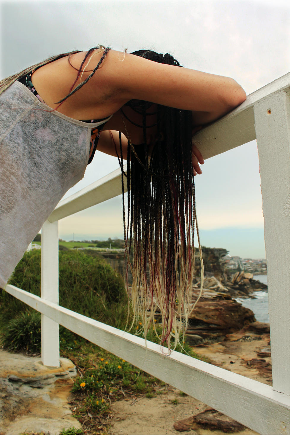 [image description: Ria is leaning her head and crossed arms on a white fence. She has long, brown braids which are magenta and blonde at the tips. You cannot see her face.]