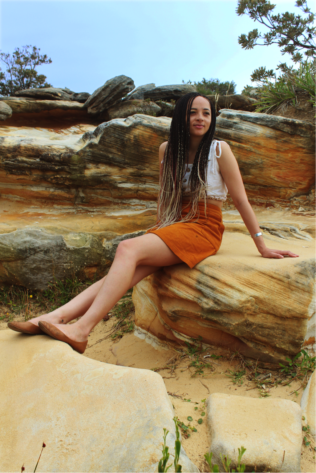 [image description: Ria is sitting on a sandstone rock, her legs are stretched out and placed on a rock in front of her. She is looking out to the distance with a relaxed expression.]