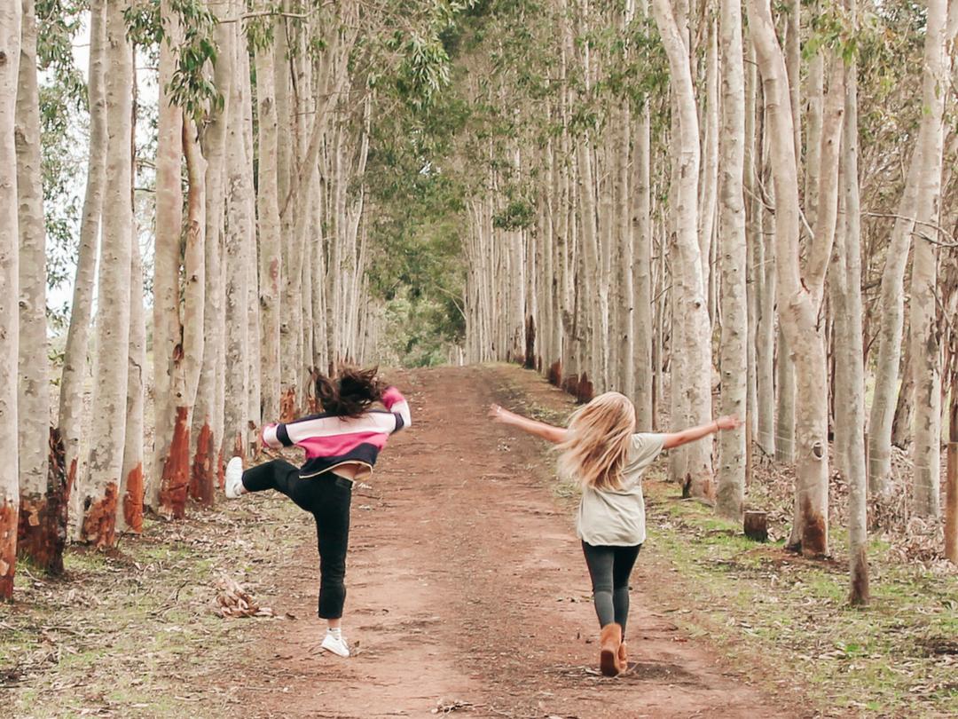 Two girls dancing between trees.png