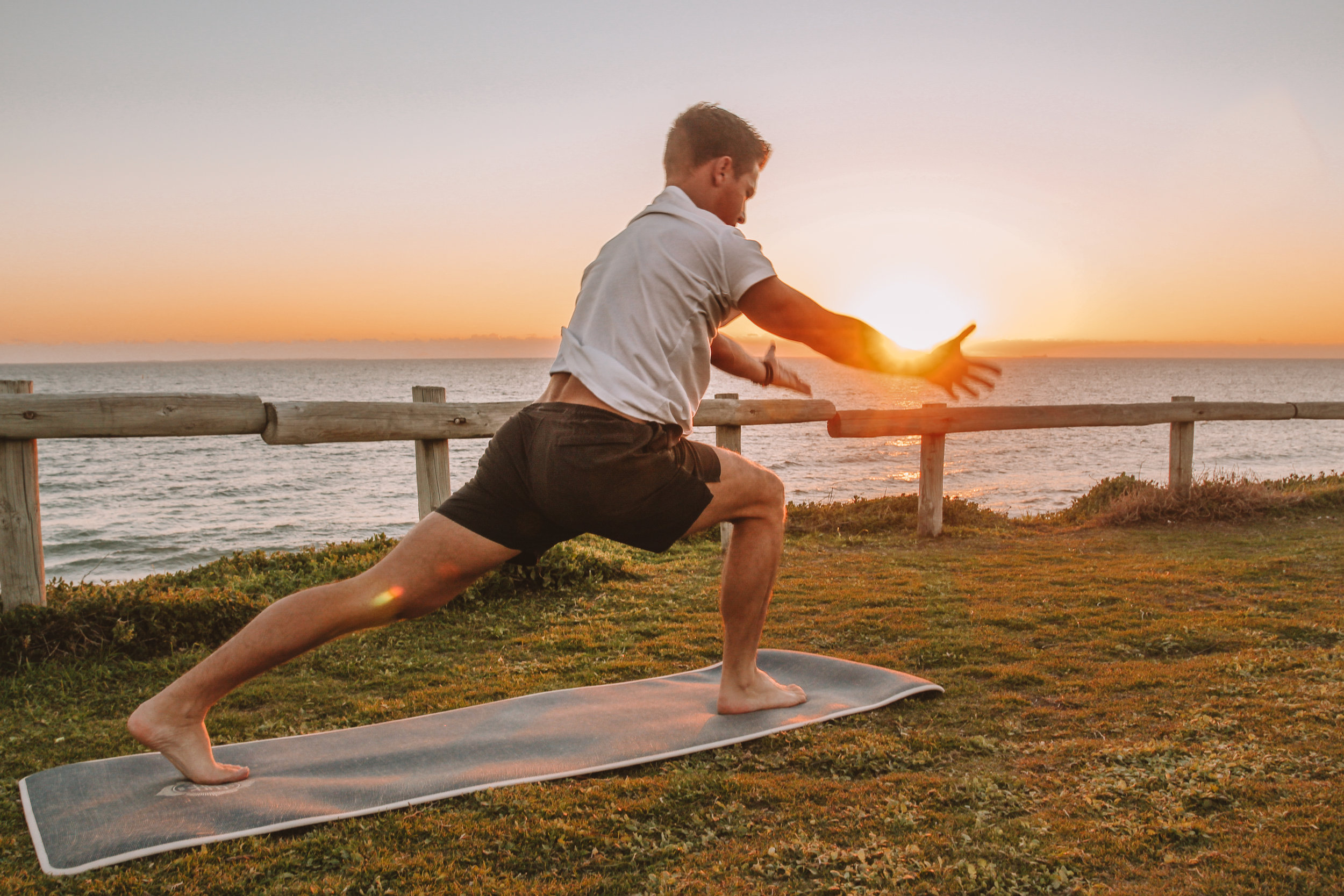 Male doing yoga by the beach at sunset.jpg