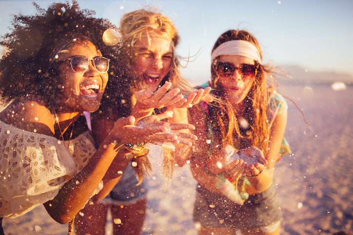 Girls-blowing-confetti-from-their-hands-on-a-beach-471881654_727x484.jpeg