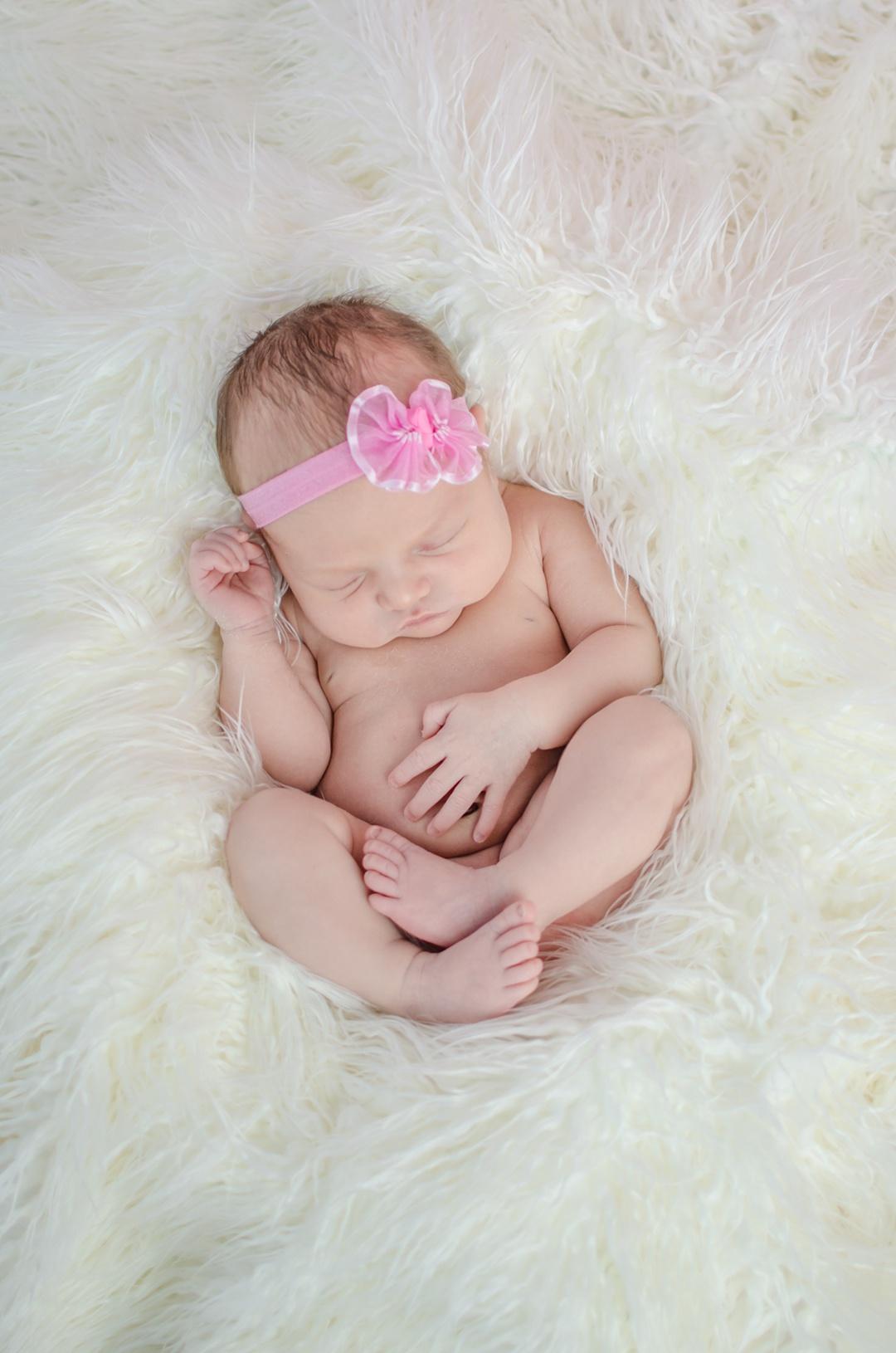 baby on white fur newborn session in louisville