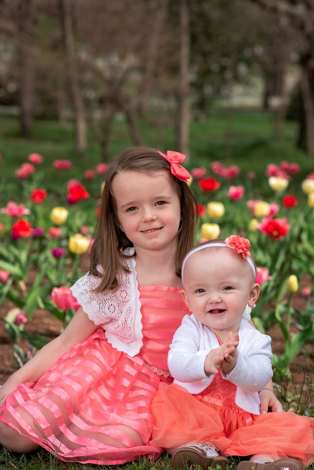 young girls pose in front of tulips in lexington for louisville family photographer
