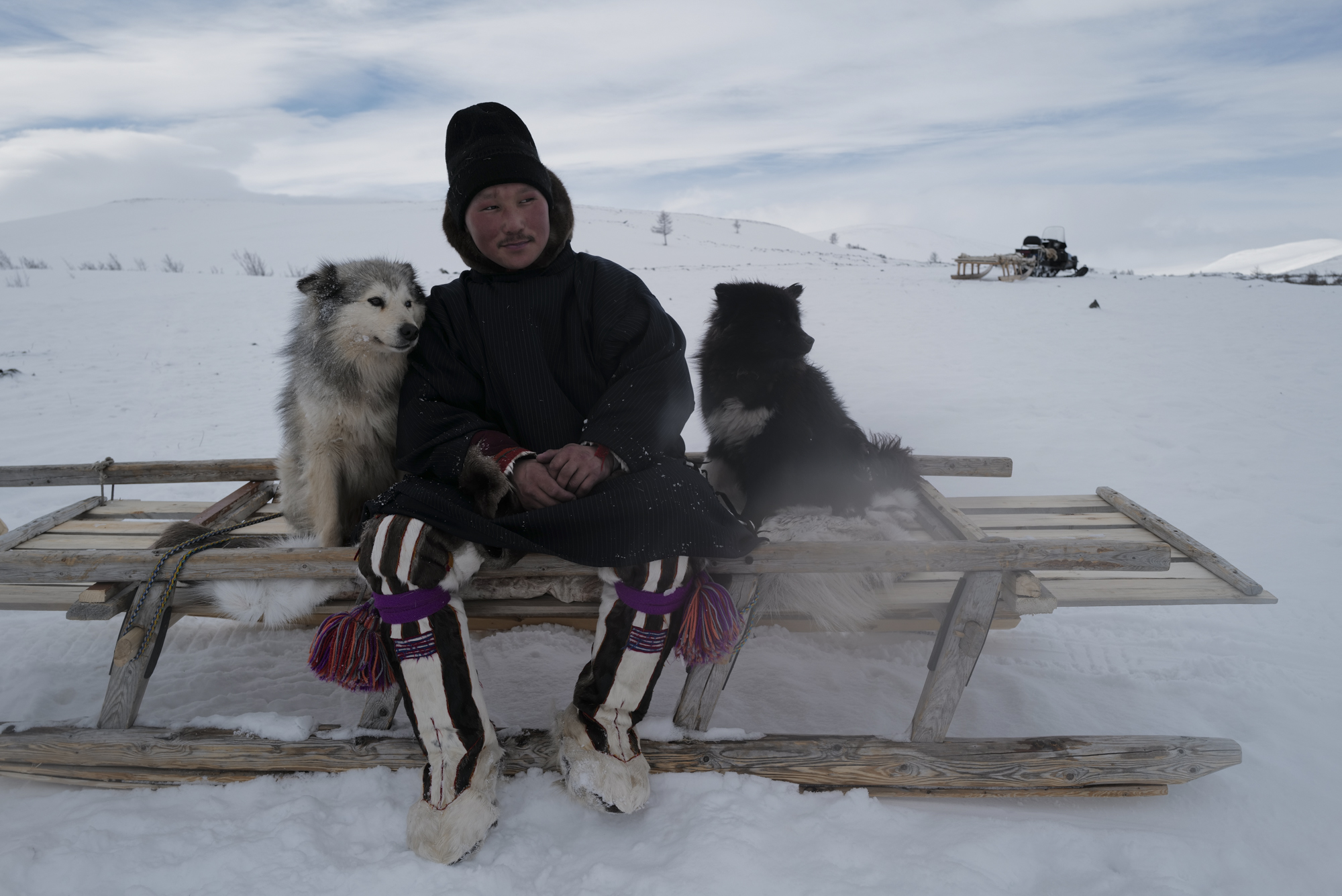 Aleksander with his loyal Samoyed dogs. These dogs help to herd their reindeers and pull their sleds. Photographed with Leica Q2, Siberia, 2019.  ©  Rosalynn Tay.