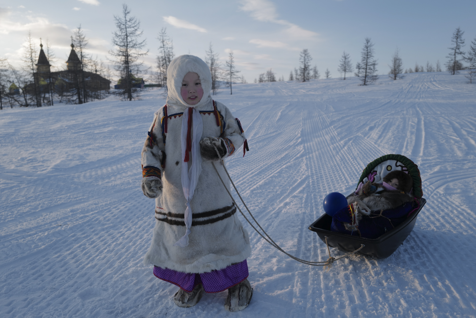 A Nenets schoolgirl pulling her baby sister in a sled-like pram. Photographed with Leica Q2, Siberia, 2019.  ©  Rosalynn Tay.