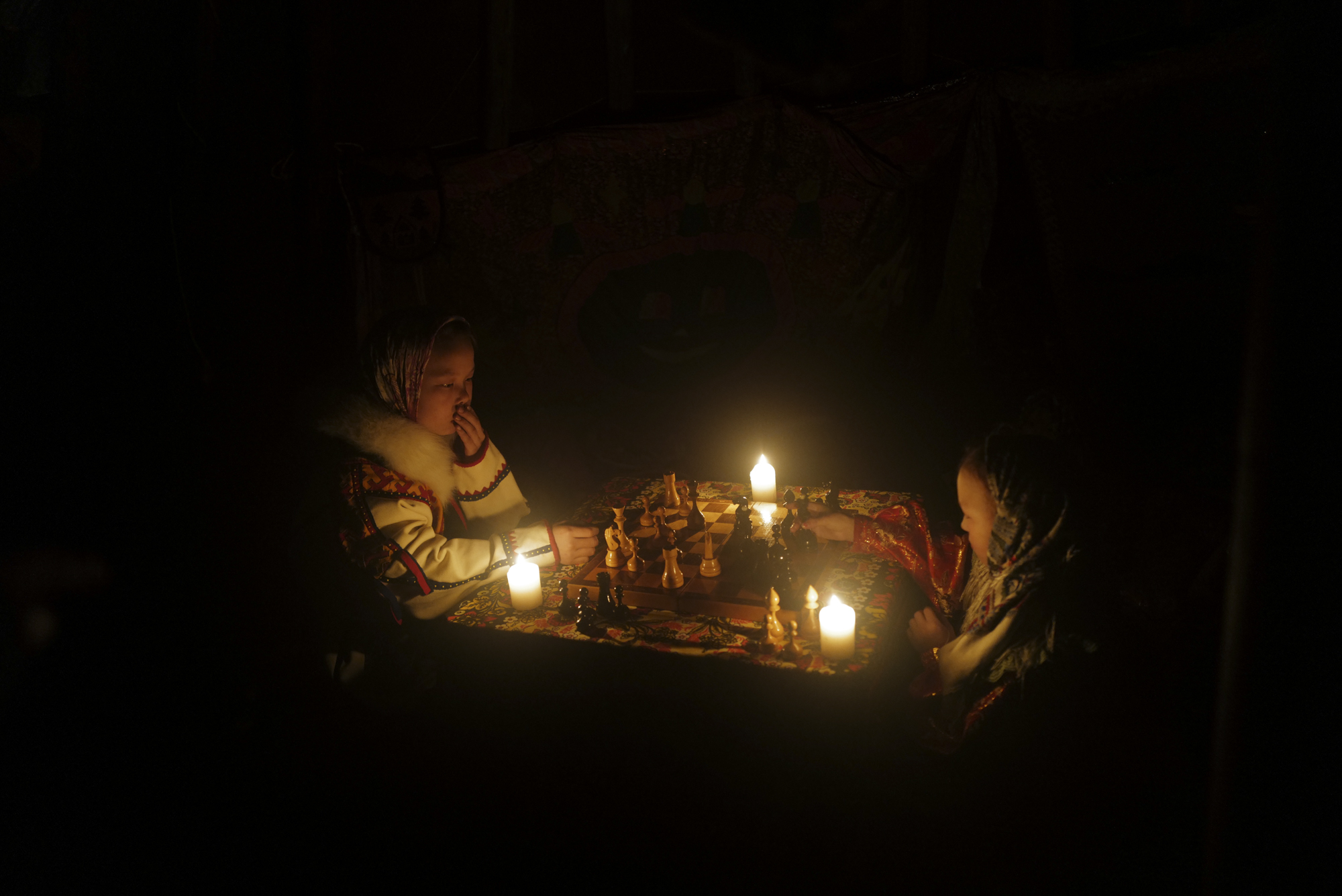 Two Nenets school children were playing Russian chess under the candlelight. Photographed with Leica Q2, Siberia, 2019.  ©  Rosalyn Tay.