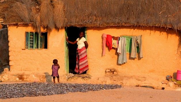 Lake Shore Lodge Tz - Lake Tanganyika - Giving back - Mvuna village with house, woman & child.jpg