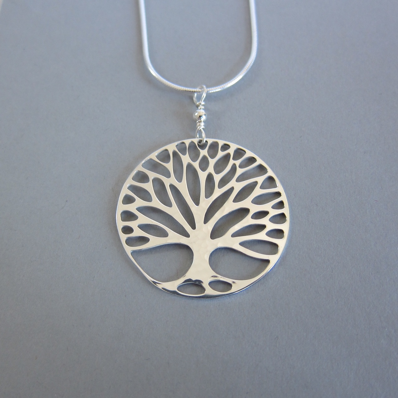 Marcia Dean - I love trees and making things! I fabricate my original design jewelry under skylights in my airy studio and fulfill several roles at the co-op which provides my work life with a balance of solitude and community, variety and routine, creativity and concrete action.My jewelry is made with gold and silver, sometimes together, and often includes opals, each one offering a unique array of brilliantly shifting colors.I also take great pleasure in creating contemporary quilts. The entire process satisfies me from surface design to meditative hand quilting.
