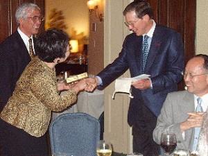 Photo: NBF President Felix Laughlin presents a memento of her visit to Mrs. Takeko Yamaki Tatsuzaki as her husband (left) and NBF guest Mr. Hiromasa Oguchi joyfully observe.