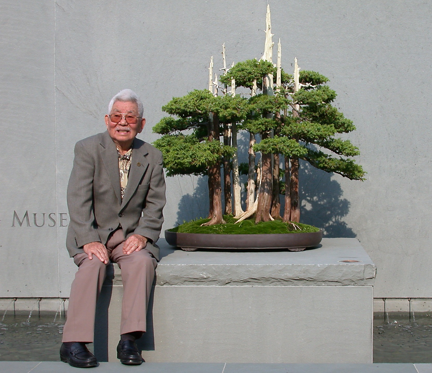 """John Naka pictured with """"Goshin"""" at the entrance to the Upper Courtyard (2003)"""