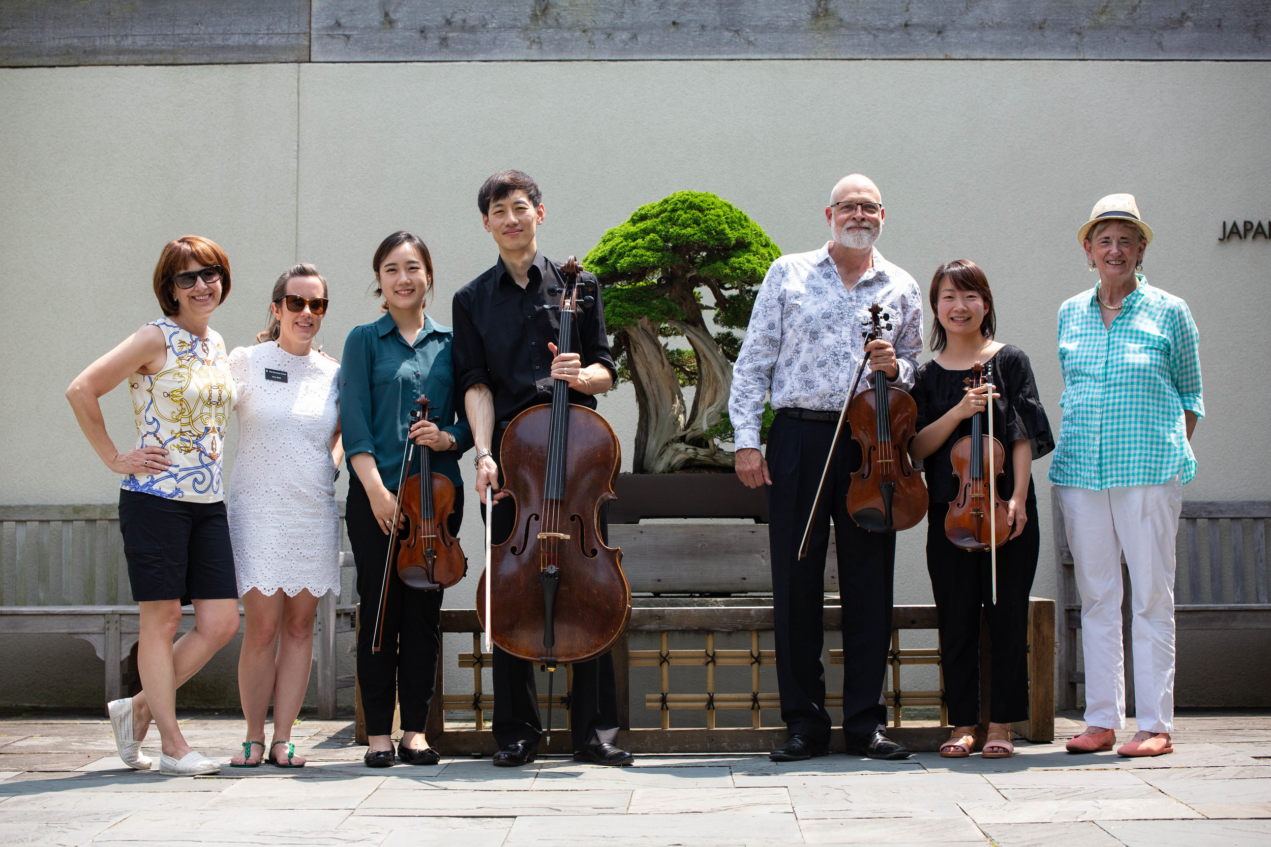 (L-R) Janice Vitale (NBF Board Member), Amy Grossnickle (Kennedy Center), NSO Musicians, Johann Klodzen (NBF Executive Director) posed with the Juniperus chinensis var. Itoigawa (donated by the Kennett Collection).